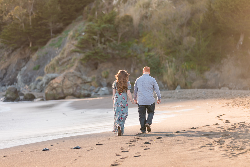 Muir Beach sunset engagement session couple walking alone the beach in the beautiful sunlight