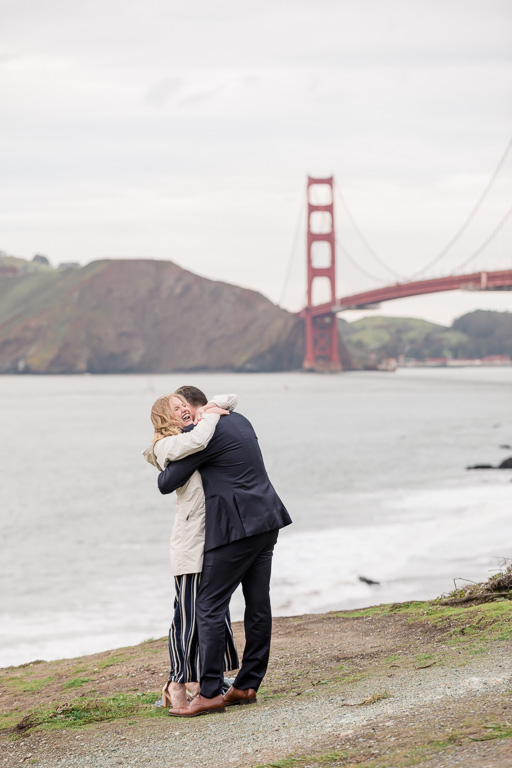 a big hug after she said yes to his proposal in front of the Golden Gate Bridge
