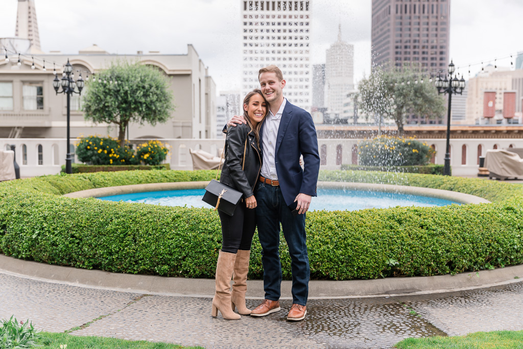 happy newly-engaged couple in front of Fairmont Hotel outdoor fountain
