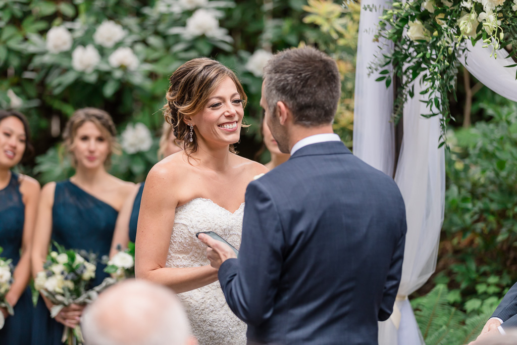 bride smiling at groom when he reads his touching vows