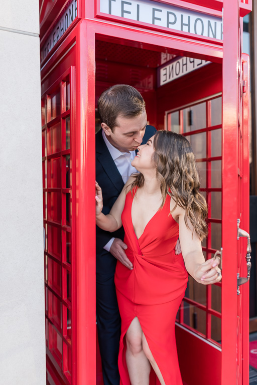 couple kissing inside the bright red photo booth