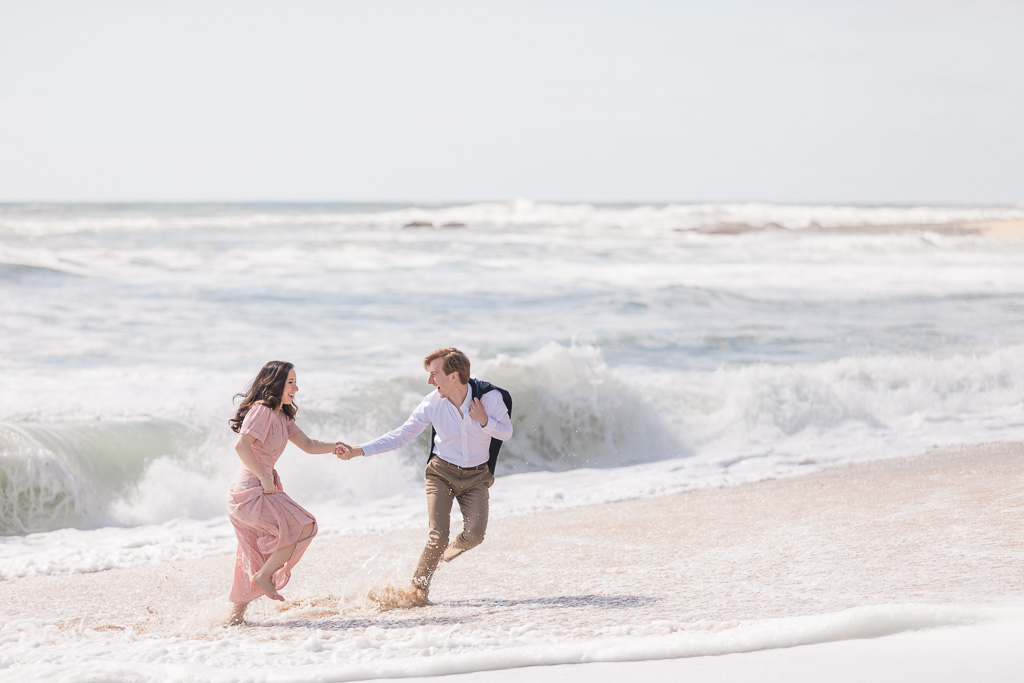 San Francisco happy engagement photo playing in the ocean running on the beach