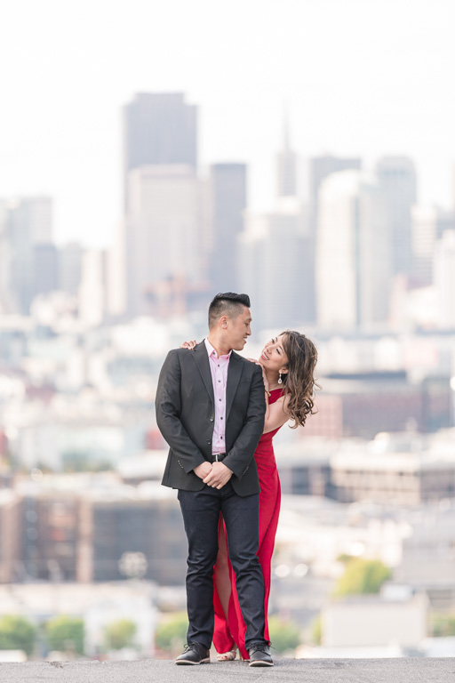 couple standing at a hill overlooking SF skyline
