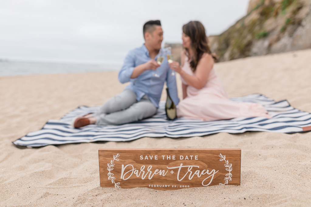 San Francisco save the date photo on the beach with a cute wooden engraved sign