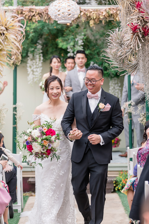 newlyweds walking down the greenhouse aisle after tying the knot