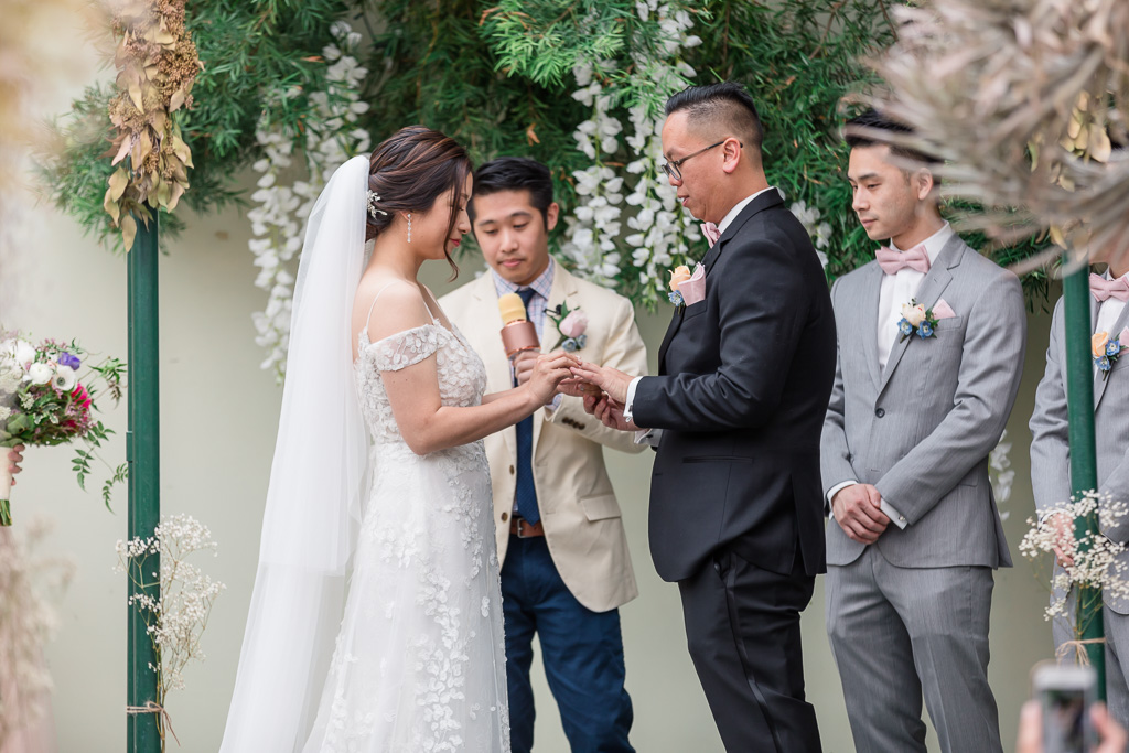 couple exchanging wedding rings in front of the orchids