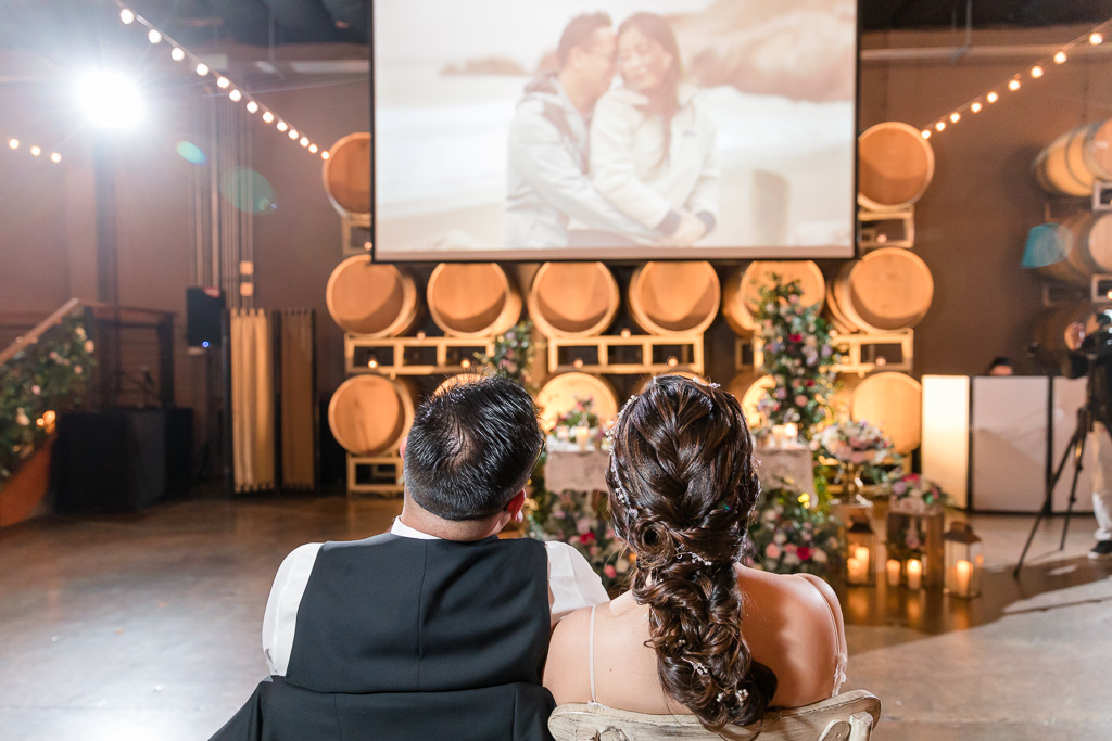bride and groom watching their San Francisco wedding same day edits at reception