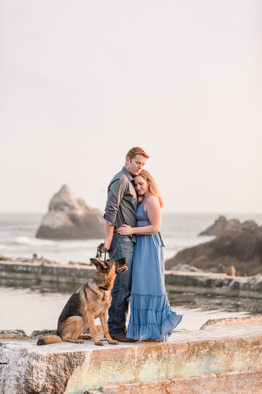 sweet engagement photo with cute dog by the water