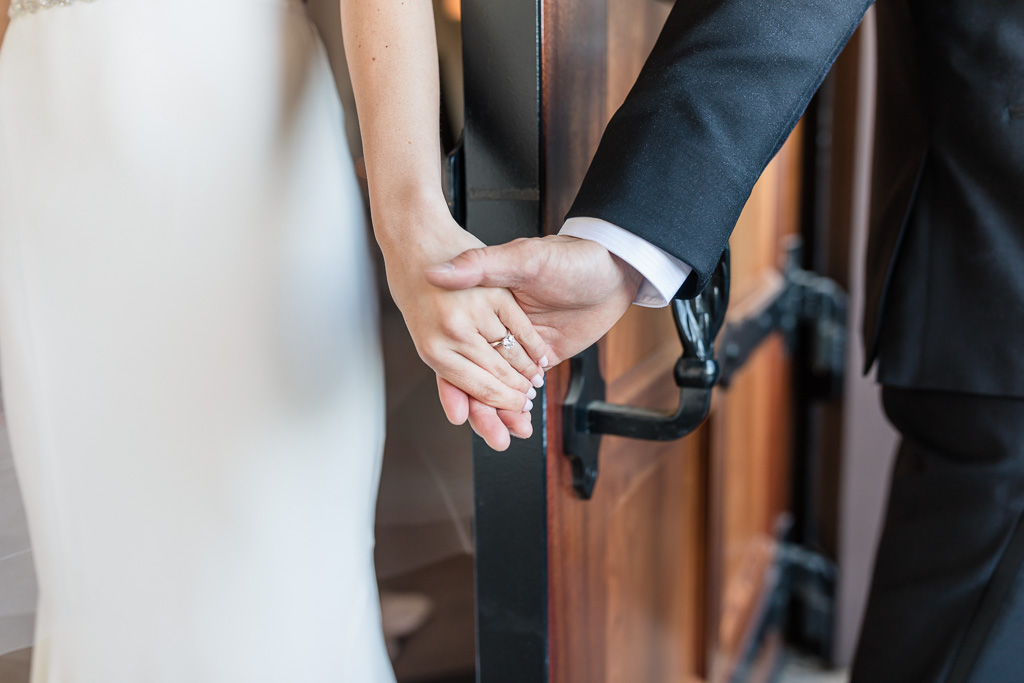 bride and groom first touch by holding hands before their ceremony