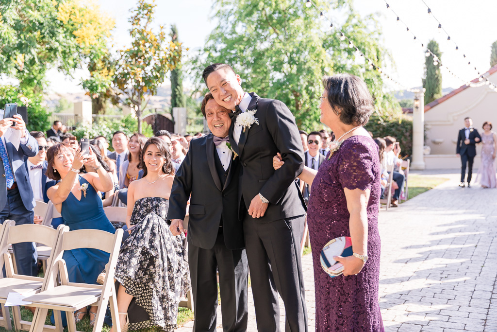 groom hugging parents at the end of the aisle