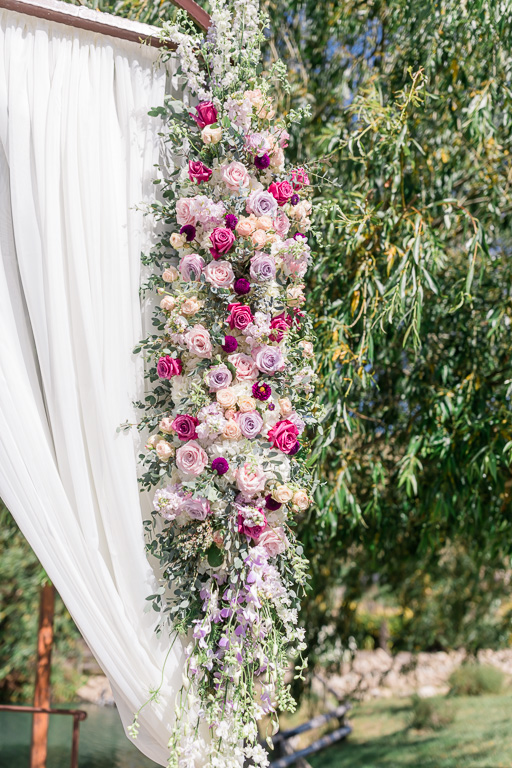 elegant floral arrangement for outdoor wedding ceremony by the pond and mountains