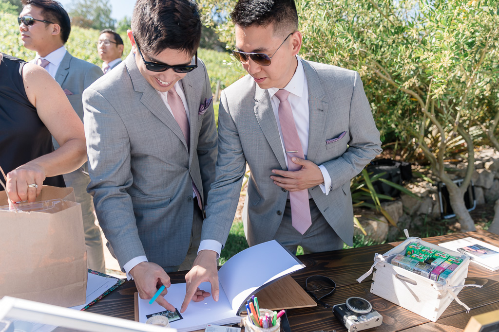 groomsmen putting their names down in the sign-in book