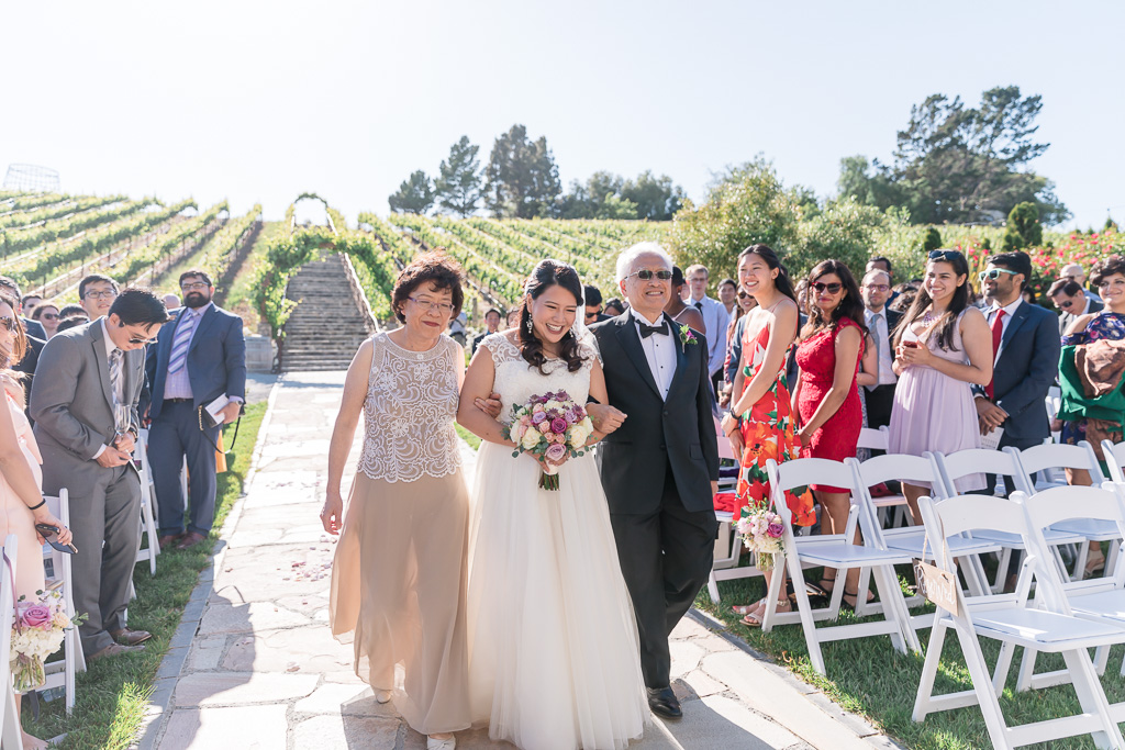 bride being escorted by her parents down the aisle
