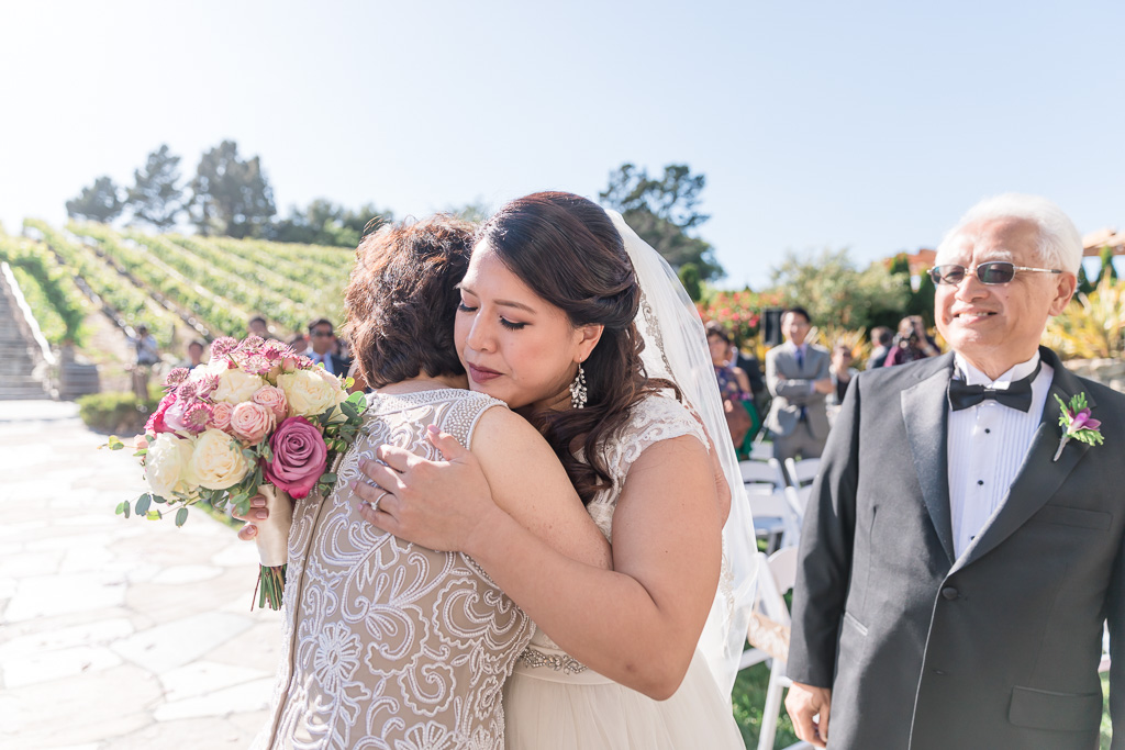 bride hugging her parents at the end of the aisle