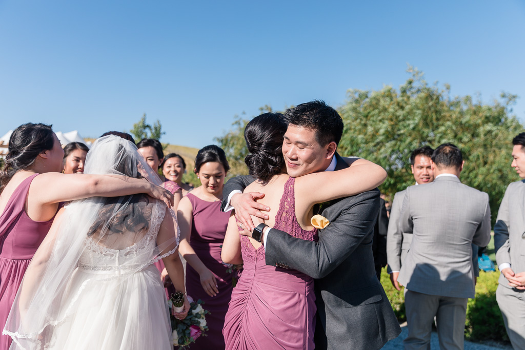 bride and groom celebrating and hugging the wedding party