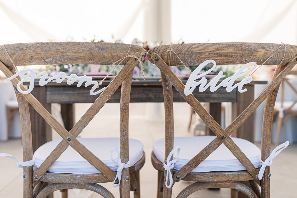 wooden groom and bride signs hanging on the chairs