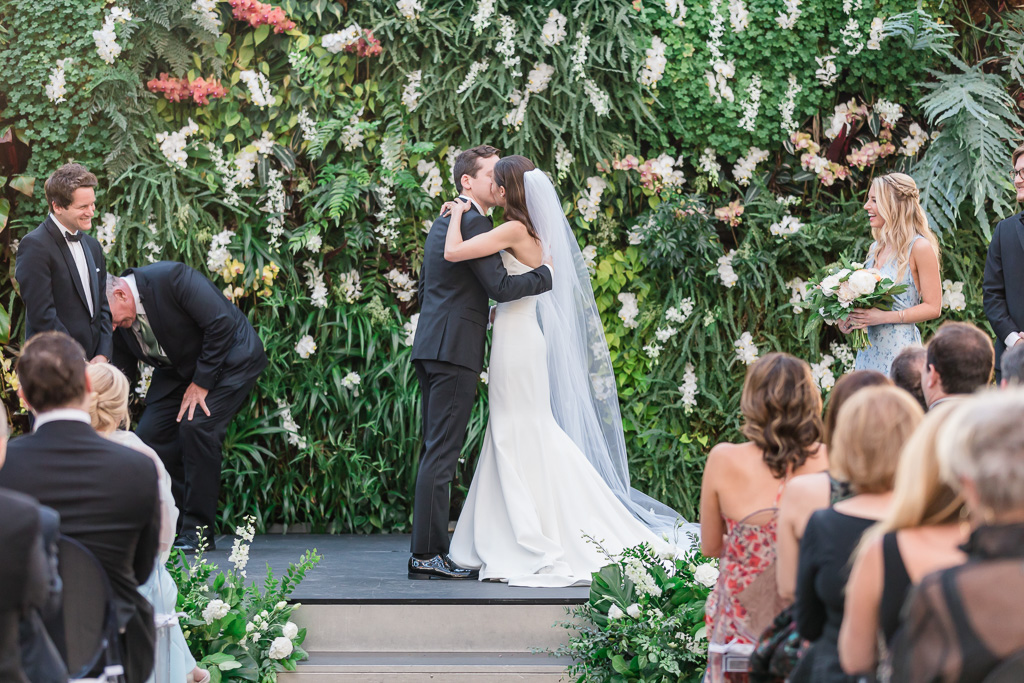 first kiss as husband and wife in front of the living planted wall