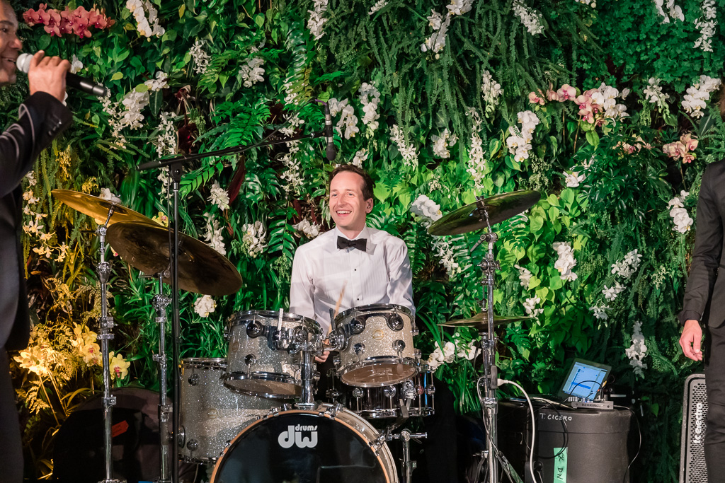 groom plays the drums at his own wedding reception party