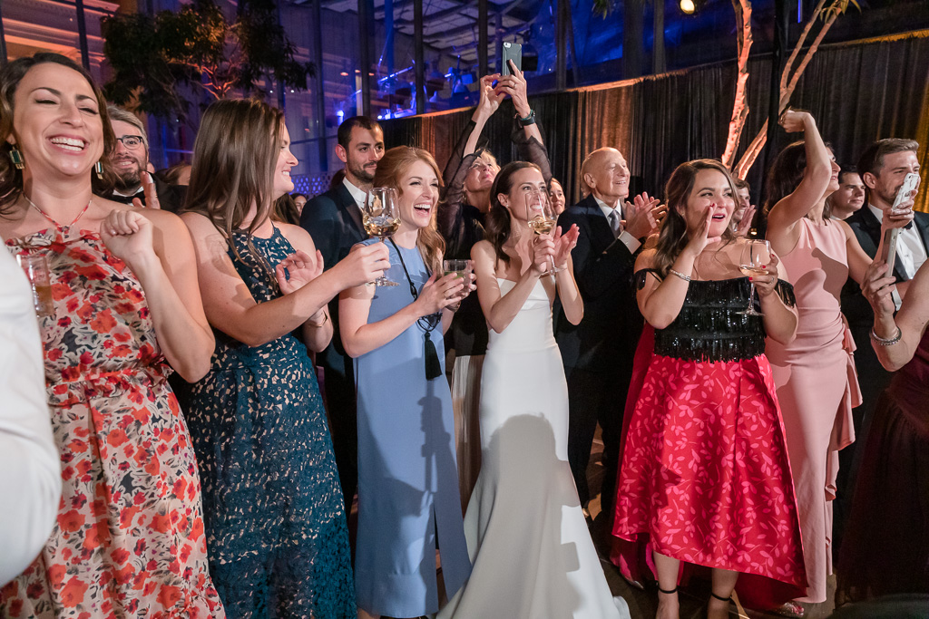 bride and guests cheering for the groom