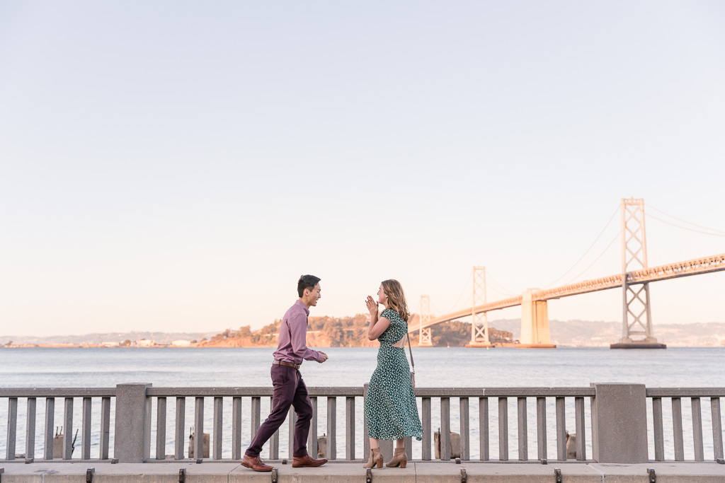 he is about to bend down on one knee and ask her to marry him in front of the bay bridge