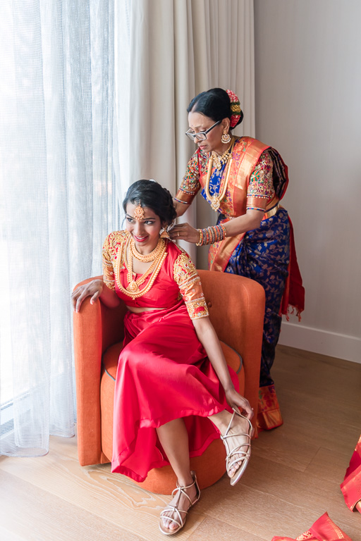 mother helping the bride to get in her sari