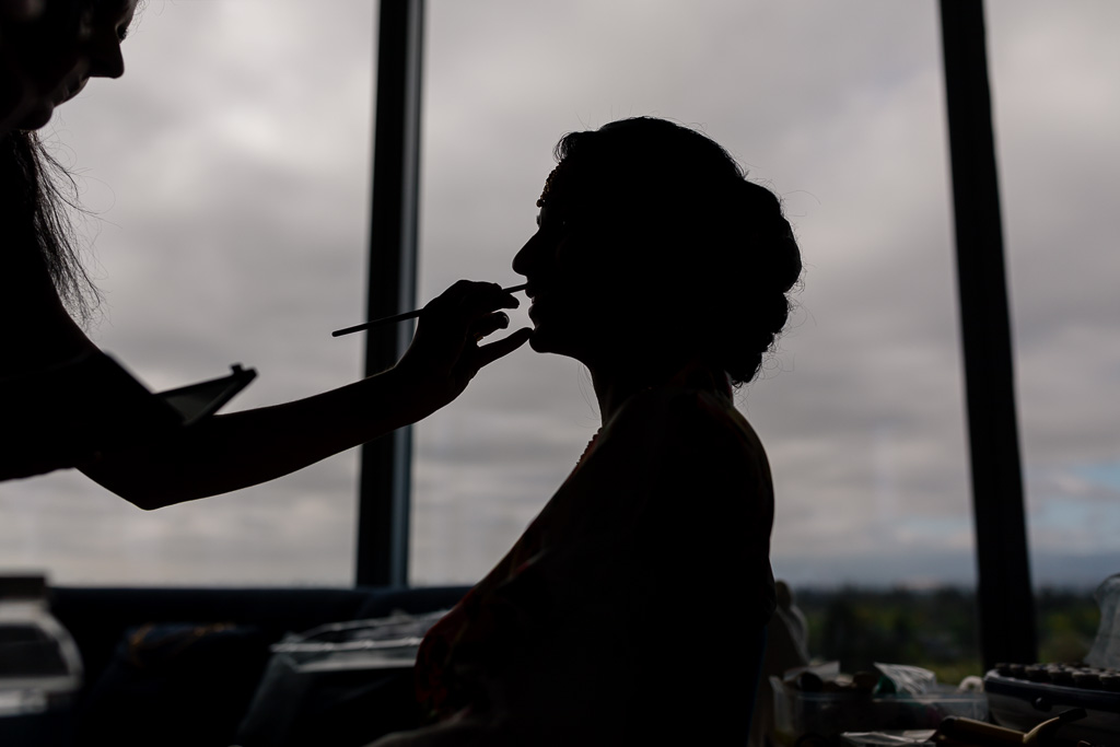 silhouette picture of the bride getting her makeup done