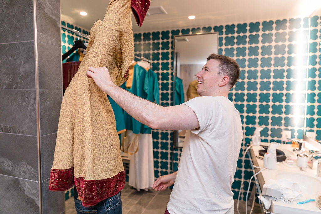 groom getting into his Indian gown dhoti