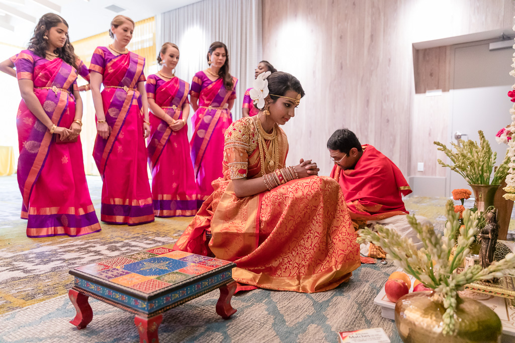 bride praying while the baraat is happening outside