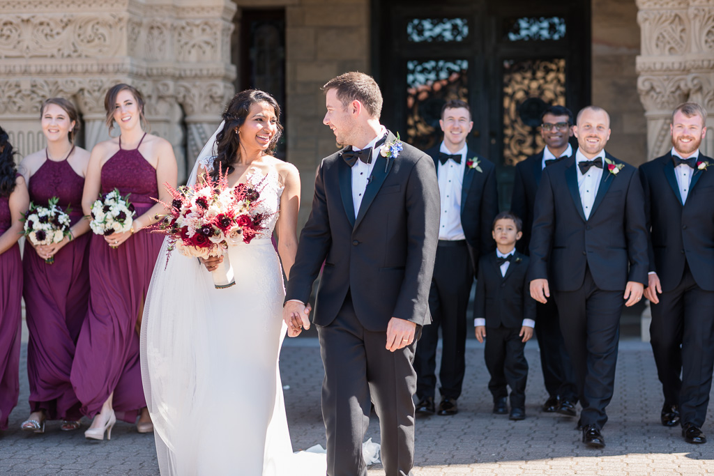 newlyweds with wedding party walking outside the church