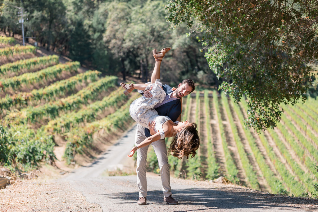 playful and lively engagement photo in front of vineyards