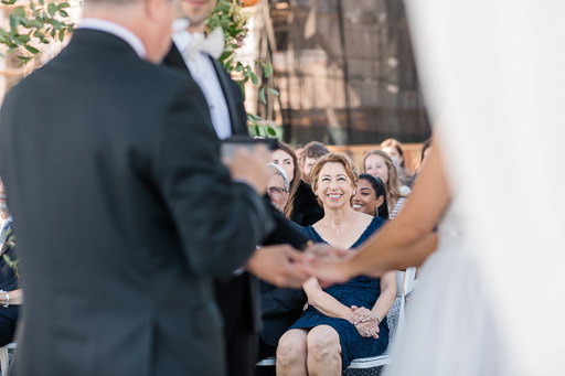 groom's mother smiling at the couple during vow exchange