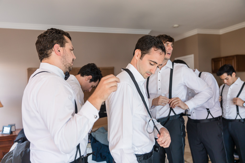 groom getting ready with the help of his groomsmen