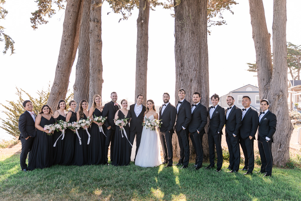 trendy wedding party wearing black dresses and tux