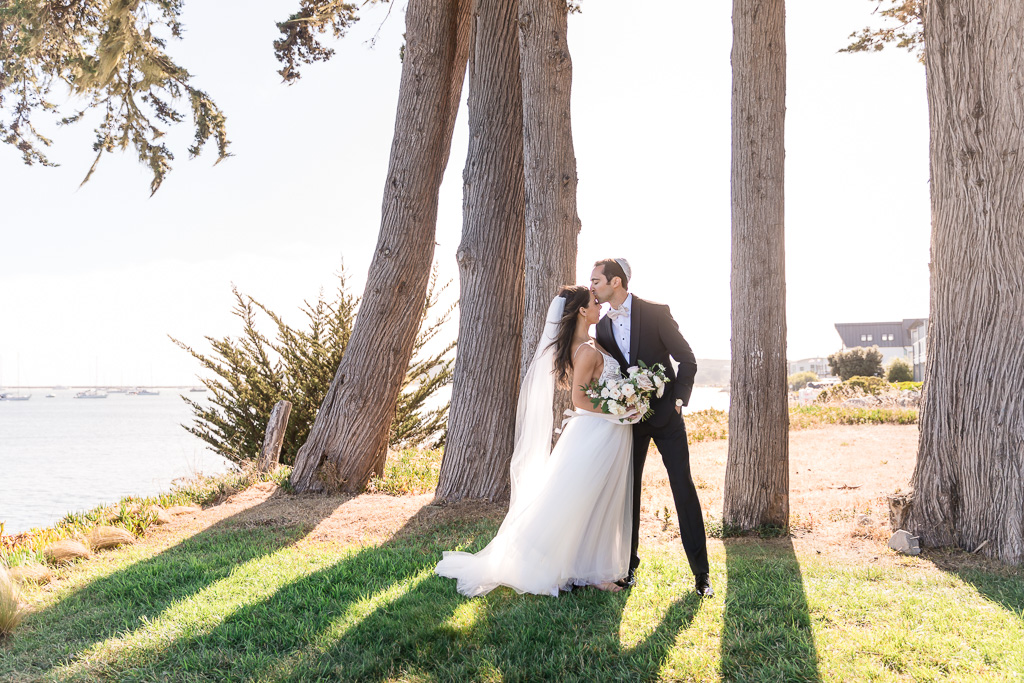Half Moon Bay wedding sunset photo by the water with sunlight shining through the trees