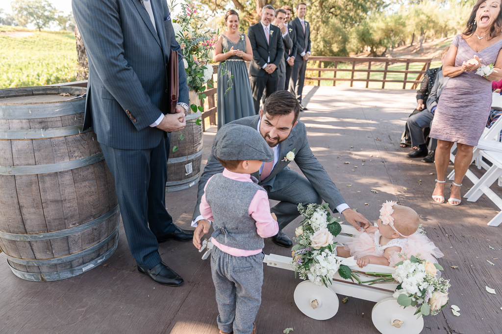 ring bearer pushes the cutest baby flower girl in a floral wagon