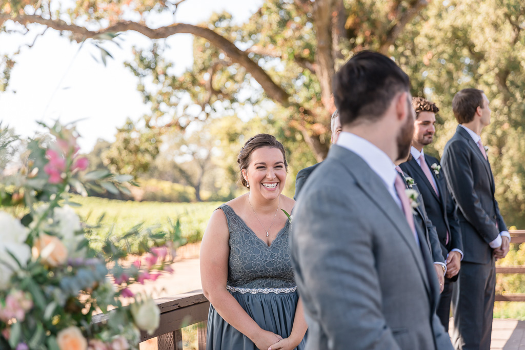 groom and sister laughing during ceremony