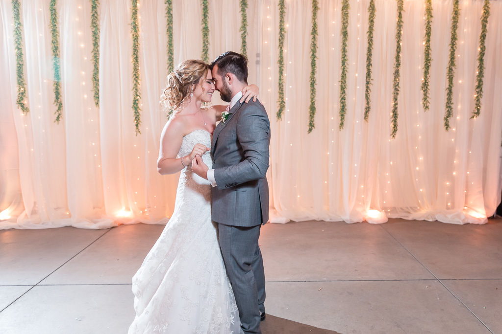 first dance in front of the lit-up draping