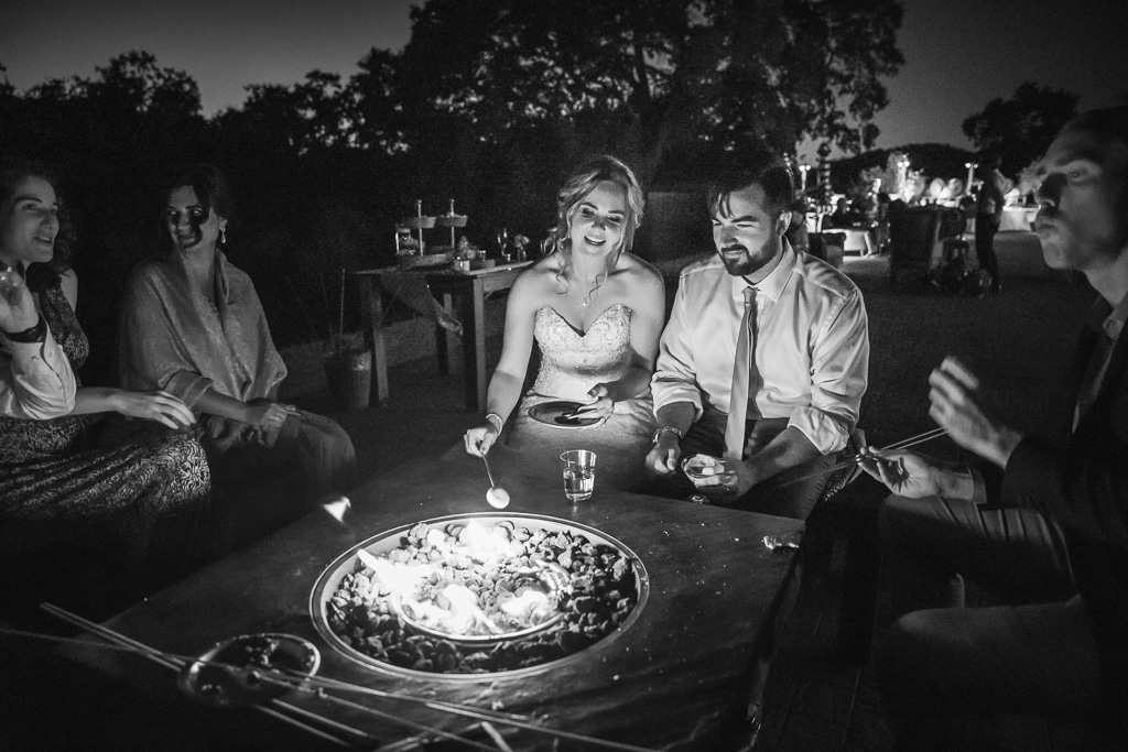 bride and groom at the s'mores fire pit with their wedding guests