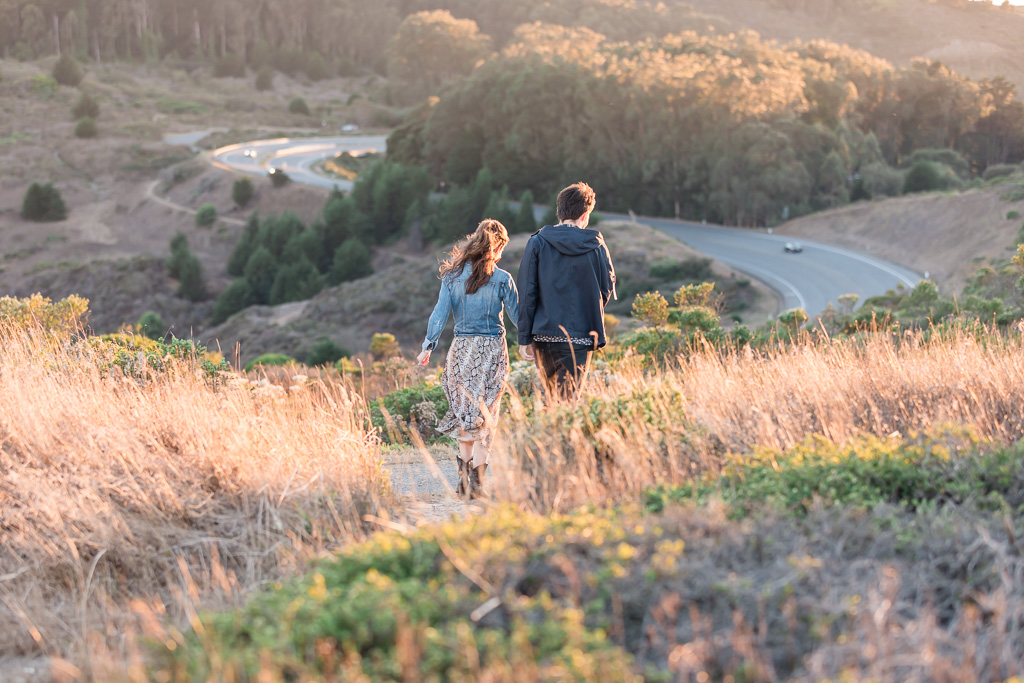 newly engaged couple walking down the hill