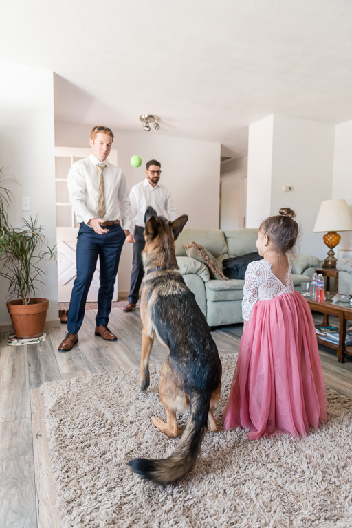 groom and flower girl playing fetch with the dog ring bearer
