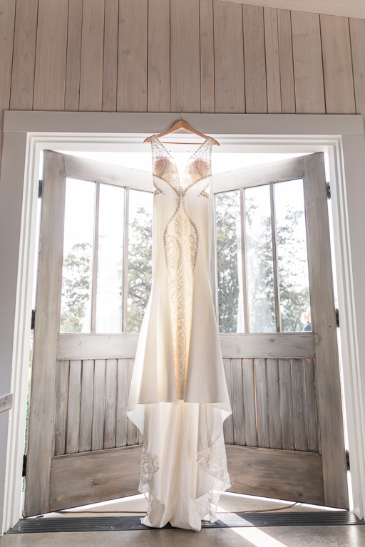 see-through wedding gown hanging in the bridal suite