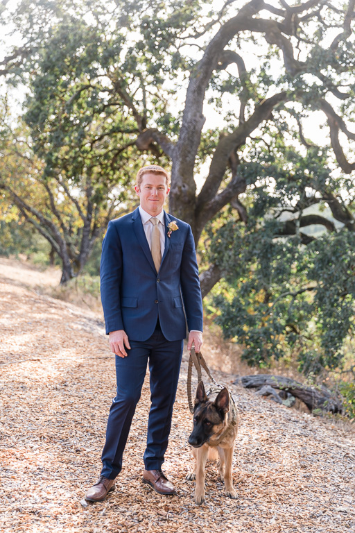groom and his dog ready for the first look