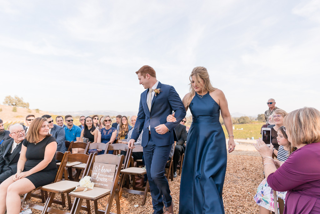 groom walking down the aisle with his mother