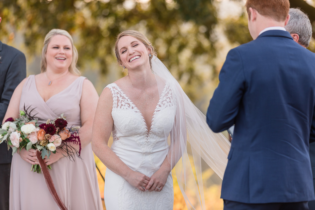 bride laughing to groom's funny vows