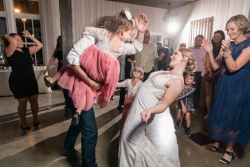 bride and groom dancing with their flower girls