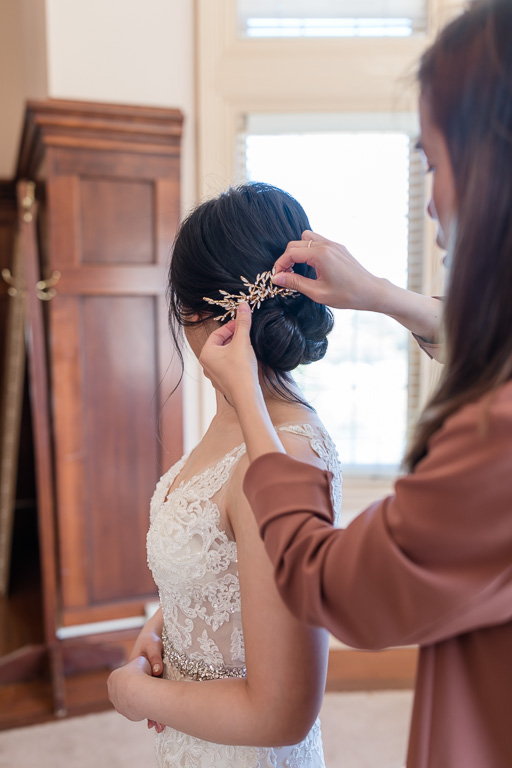putting on hairpiece on the bride's updo