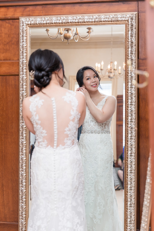 bride putting on earrings for herself