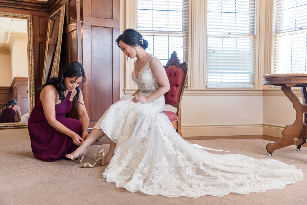 cute getting ready moment when bride putting on shoes