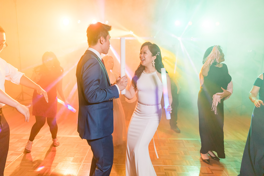 bride and groom dancing in the colorful lights
