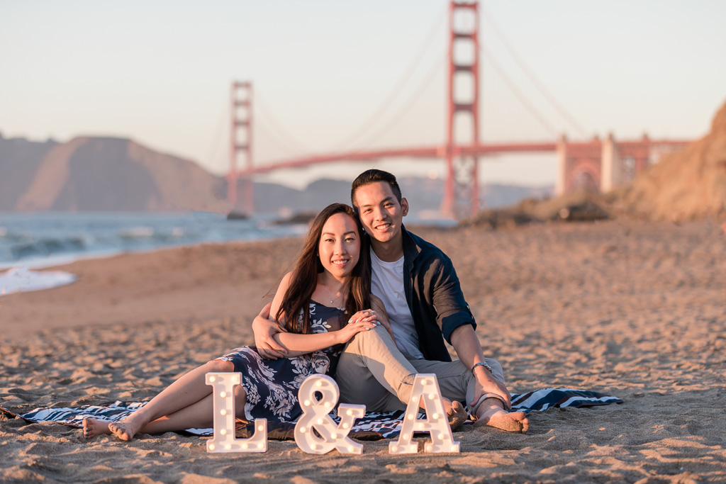 save-the-date picture on the sand in front of Golden Gate Bridge